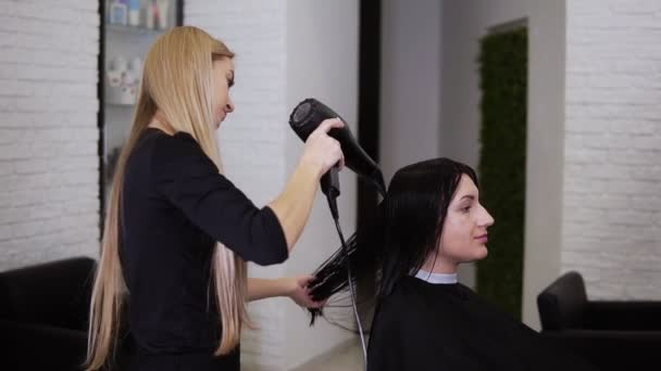Caucasian brunette young woman get her hair dry by beautician barber after before the new haircut in hairdresser salon. Beauty industry. Side view