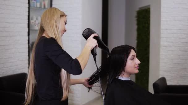 Kaukázusi barna fiatal nő kap a haja száraz kozmetikus borbély előtt az új frizura fodrász szalonban. Szépségipar. Oldalnézet