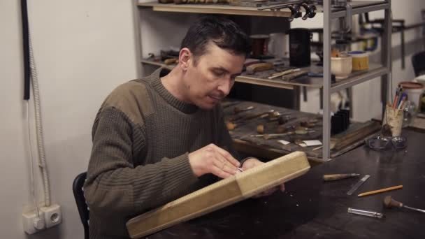Caucasian joiner makes notches on the wooden workpiece with curved chisel. A craftsman carving wooden ornament on backgammon sitting in his working place. Slow motion