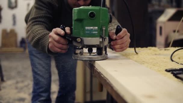 Nerozpoznatelný muž tesař pracuje s drtičem, leští dřevěnou tyč. Rozdrtí velké dřevěné prkno. Zpomalený pohyb