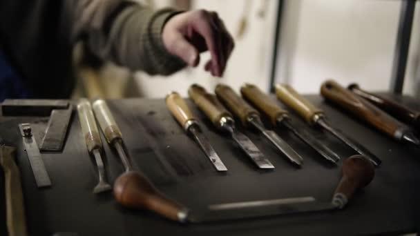Dřevoobráběcí a řemeslné nástroje. Tesařské ruční nářadí. Hoblíky, dláta, měřicí nástroje. Pohled z police, když si mistr vezme konkrétní nástroj