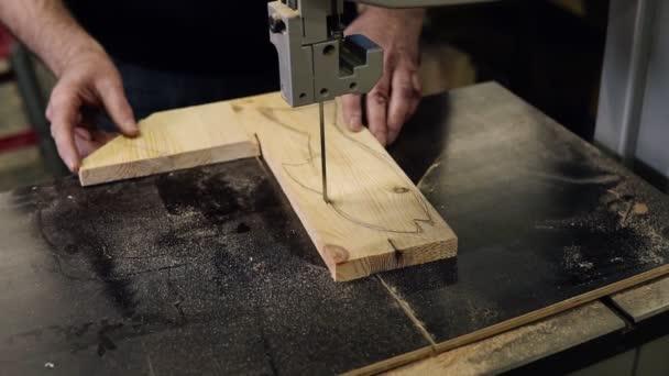 Detailní záběry mužských rukou pracujících s elektrickým řezacím strojem. Vysokoúhlé záběry muže řežícího dřevěný vzor ve tvaru ryby na stole