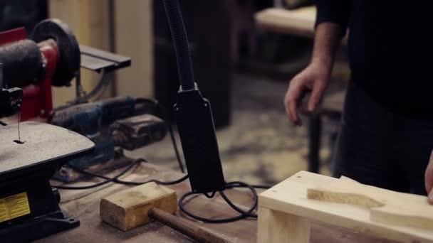 Nerozpoznatelný člověk připojí zařízení k elektrické energii, položí svou podobu na lavičku a začne brousit vzor tvaru ryby bruskou. Detailní záběr člověka, jak brousí dřevo v dílně. Pomalé