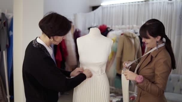 Dva profesionální krejčí, designéři pracující s novým modelem krejčovských bílých šatů na figurínu ve studiu, ateliér. Upevnění rukávů a přišpendlení sukně. Módní a krejčovská koncepce. Zpomalený pohyb