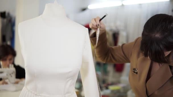 Moderní šicí studio, koncentrovaná brunetka žena módní návrhářka měřící rukáv z bílého obleku na figuríně a dělat si poznámky držící svůj zápisník. Zpomalený pohyb
