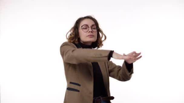 Porträt eines Mädchens mit lockigem Haar mit stylischer Brille, sie tanzt komisch vor Freude. Überrascht aufgeregte fröhliche Frau lässt funky Stil tanzen. Europäische weibliche Modell in lässig auf weißem Hintergrund