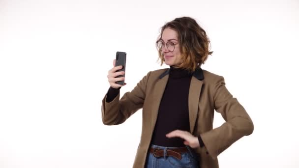 Charming trendy young woman with curly short hair having video chat through phone and laughing, talking standing isolated on white background. Wearing brown jacket and eyeglasses