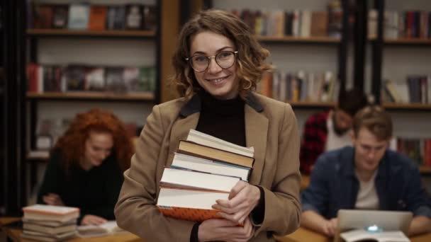 Portrét atraktivní evropské studentky, držící knihy v knihovně střední školy a usmívající se na kameru. Koncept vzdělávání, literatury a lidí. Spolužáci na rozmazaném pozadí
