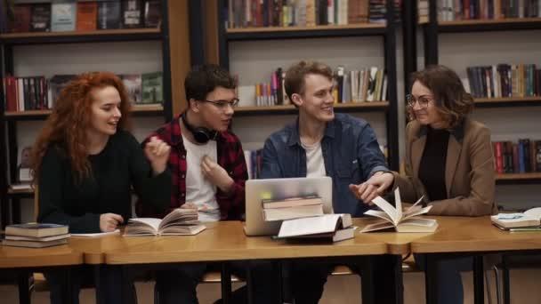 Skupina mladých studentů, kteří mluví pomocí notebooku a vysvětlují spolu práci na kurzu v knihovně. Aktivně o něčem diskutovat, smát se a gestikulovat. Sedí u dřevěného stolu. Zpomal. Pohled zepředu
