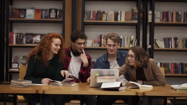 Group of young students talking using laptop explaining course work study together in library. Actively discussing something, laughing and gesturing, looking at the camera. Sitting by wooden table