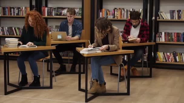 Gruppe von Studenten, die sich auf die Prüfung in der Universitätsbibliothek vorbereiten, zwei schöne Frauen, die Notizen machen, zwei Kollegen hinter dem Buch, die am Laptop arbeiten, konzentrierte Studenten im Lernprozess