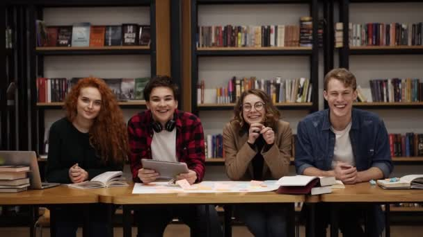 Two young male and two female european students sitting at the table with books and laptop in the library and cheerfully smiling. Bookshelves in library with lots of books in background