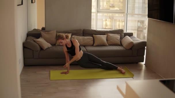 Žena cvičení doma cvičit různé jóga asany, dělat dolů čelí psa pózovat v obývacím pokoji na žluté podložce. Zpomalený pohyb