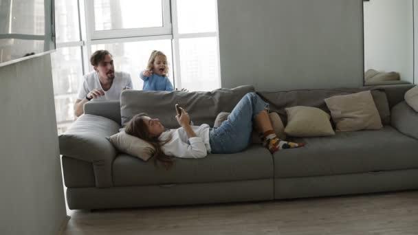 Im Wohnzimmer liegt müde Mutter auf Sofa mit Smartphone, entzückende Tochter und Vater erscheinen plötzlich von der hinteren Couch und erschrecken Mutter. Paar und Kind gemeinsam zu Hause Spaß haben, genießen