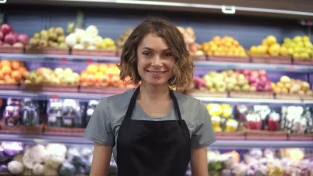 Porträt einer attraktiven jungen Verkäuferin in schwarzer Schürze, die im Supermarkt steht, mit Obstregalen im Hintergrund, in die Kamera schaut und lächelt. Gewerbe und Menschen