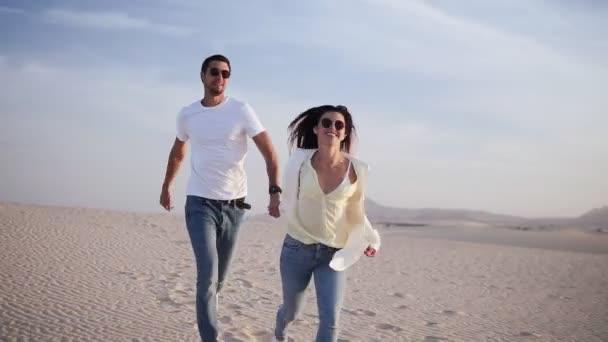 Paar Händchen haltend beim Laufen, Spaß unter der Sonne in verspielter und romantischer Beziehung unter Sonne und blauem Himmel in der Wüste. Zwei junge Liebende, die sich im Sommer auf Romantik freuen. In Freizeitkleidung