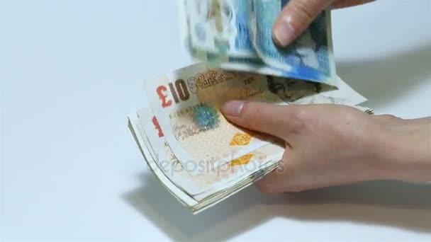 Člověk počítá peníze. Detail samice ruce počítání liber bankovek různých nominálních hodnot. Pět, deset, dvacet liber směnky v balíku. GBP. bílé pozadí