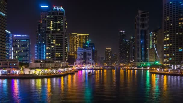Scenic view of the skyscrapers of Dubai Marina with bright night illumination and a water canal with floating yachts, time lapse, Dubai, UAE