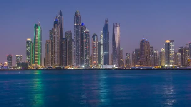 Dusk to night transition of Dubai Marina cityscape, View from Palm Jumeirah, time lapse, United Arab Emirates.