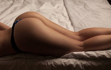 buttocks of young girls in black strings in bed
