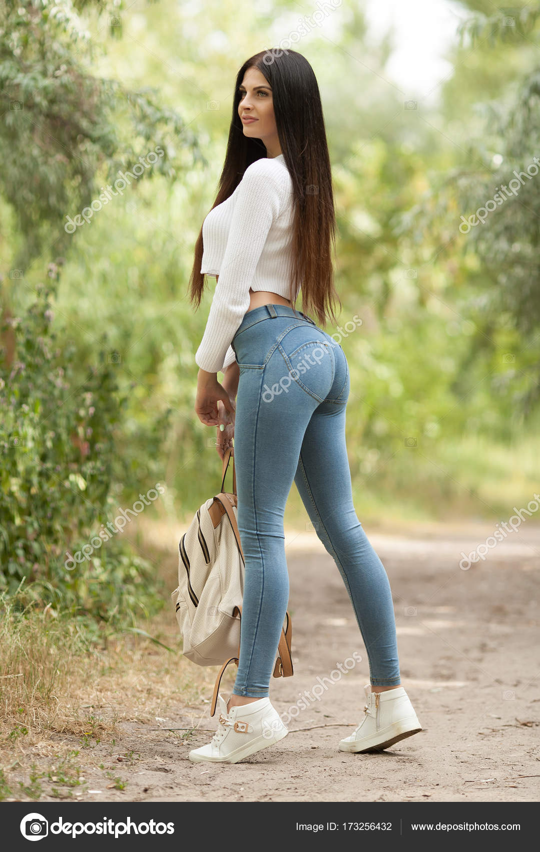 Sexy Brunette Woman In Blue Jeans With Long Hair Walk With Backpack Stock Photo