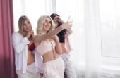 Fotografie Cheerful attractive women in pajamas making selfie in bedroom.