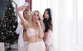 Vidám vonzó nők pizsamában, így selfie a hálószobában.