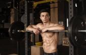 Egészséges fiatal férfi állandó, erős, rugalmas izmok - és a izmos, Athletic testépítő-Fitness modell jelentő gyakorlatok után