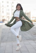 Photo Beautiful young stylish girl in a fashion green coat, white pants and white sneakers in the street on a sunny day