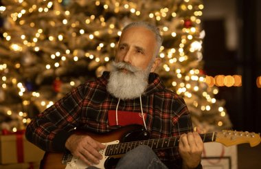 Handsome mature bearded man in casual clothes playing guitar at home near christmas tree. Xmas.