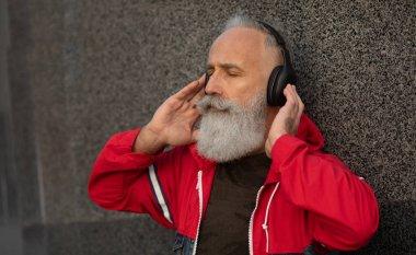 A trendy bearded senior man listening to music outdoor. Fashion mature man.