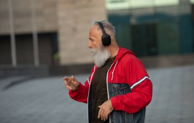 Senior crazy man listening music outdoor. Happy mature male celebrating and dancing outside. Joyful elderly lifestyle concept.