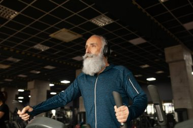 Bearded Senior Man On Running Machine In Gym. Treadmill.