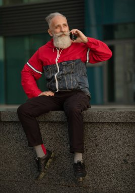 Handsome senior bearded man is talking by a smartphone while having coffee break on a street beside office building.