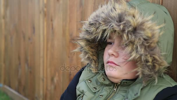 Winter portrait of cute boy in warm clothes coughing