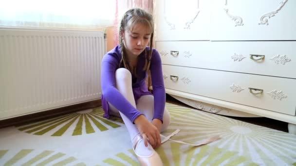 junge Ballerina sitzt auf dem Boden und zieht ihre Spitzenschuhe an