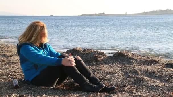 traurige Frau sitzt am Meer 2