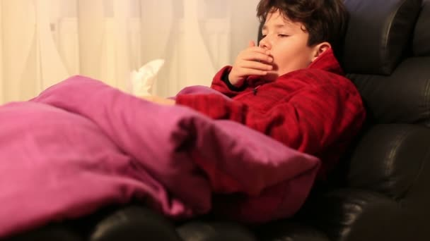 Tired, weak boy at home sick with flu lying on bed  and resting. Blows his nose in a paper handkerchief