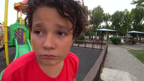 Giovane ragazzo triste al parco giochi