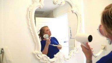 Woman drying her hair in bathroom