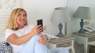 Middle aged attractive woman reading and writing smart phone on bed