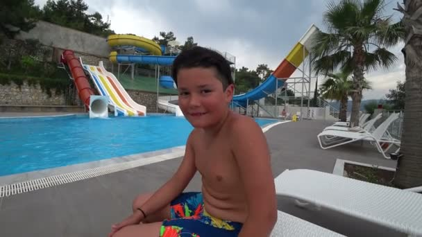 Portrait of cute teen boy in the swimming pool at aquapark looking at the camera and smiling
