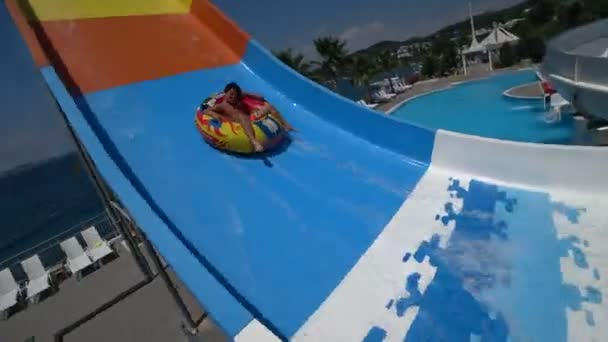 Preteen boy on water slide at aquapark