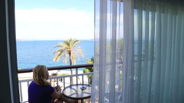 Blondine sitzt auf Balkon mit Meerblick