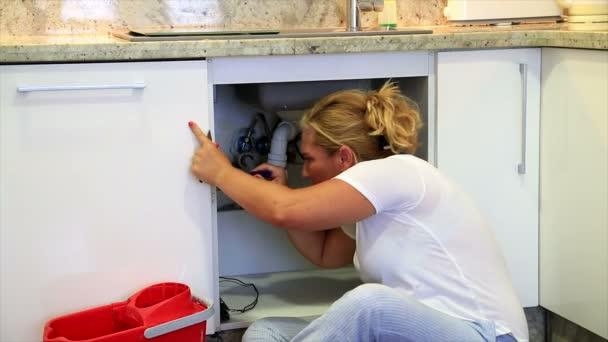 Žena upevnění dřezu v kuchyni