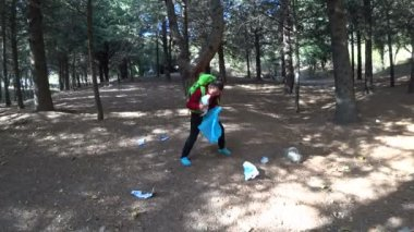 Young boy picking up trash in nature