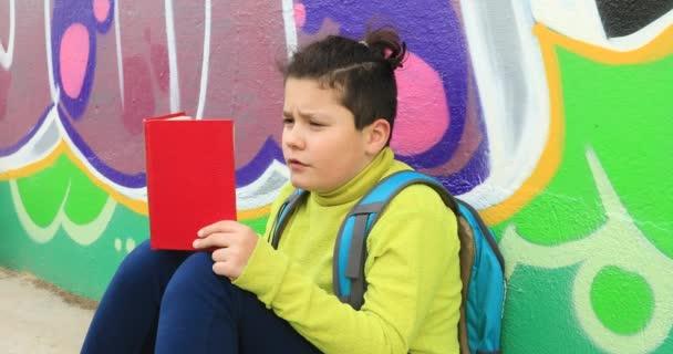 Mladý chlapec čtení knih na venkovních