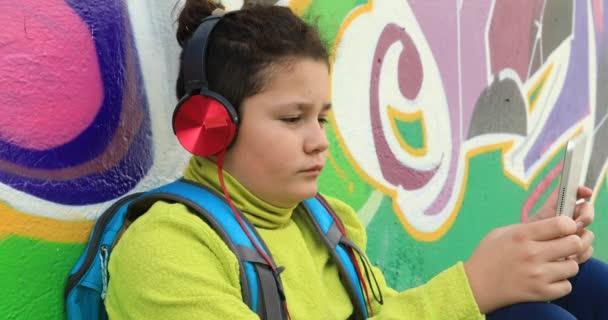 Mladík s pomocí digitálního tabletu sluchátka