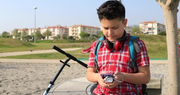 Portrait of a happy preteen boy sitting at the outdoor using smartphone  Technology, internet communication and people concept, Smartphone addiction