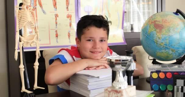 Portréja egy kaukázusi okos tanuló iskolai sok fajta kellékek néz a kamerába, és mosolyog